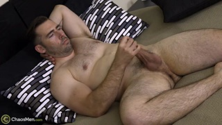 muscle man spreads his beefy thighs and jacks off
