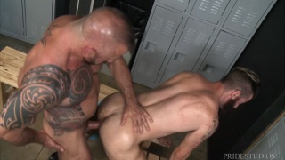muscle daddy bends bearded guy over in locker room and fucks him