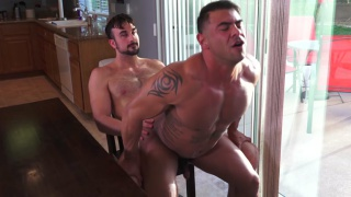 guy sits in chair while muscle hunk rides his dick