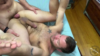 handsome bearded man holds his ankles while getting fucked