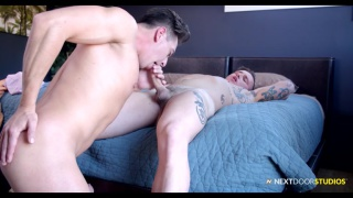 guy laying on a bed getting his dick sucked