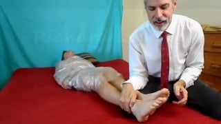 Boss Wraps Employee in Plastic & Tickles His Bare Feet