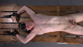 naked guy restrained to wooden rack get electro shocks