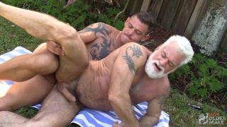 younger guy tops a silver daddy on the lawn