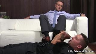 guy lies on floor & worships a man's feet