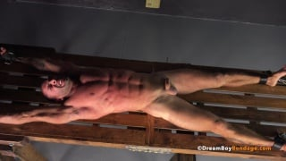 slave tied face up on rack gets whipped with a bamboo switch