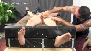 naked guy in foot stockades gets his nuts tickled