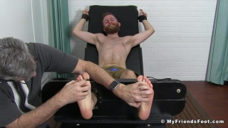 bearded ginger man gets his bare feet strapped in for tickling