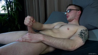 sexy bespectacled guy strokes his soldier cock