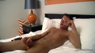 naked guy smokes & jerks his dick in bed