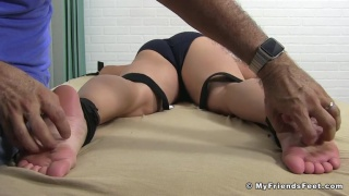 beefy guy strapped face down for foot tickling session