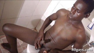 african guy sits on toilet and jerks off