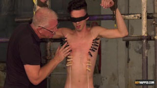 master attaches clothes pin zippers to guy's smooth body