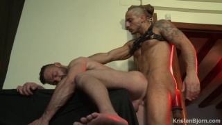 man bound to a column waits for his dominant partner