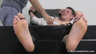 jock gets his size 13 feet in the stocks for a tickling session