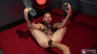 Furry Man in Leather Harness Holds His Own Legs During Fisting