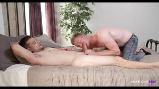 guy in jeans blows his naked buddy on the bed