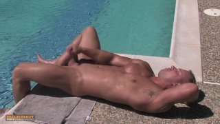 tanned hunk stroking his fat dick by the pool