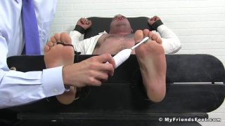 guy restrained and tickled with electric toothbrush