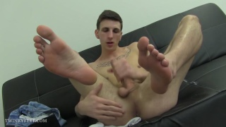 young lad rubs his bare feet together while jacking off