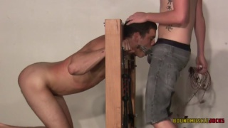 locked in stocks, slave gets his mouth filled with cock