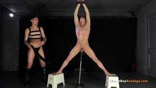 suspended naked boy stands on boxes while getting flogged