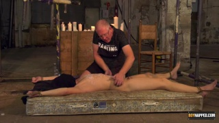 roped to a mattress, slave boy gets hot wax dripped on his body