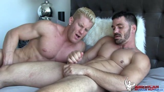 blond muscle hunk watches his buddy stroke out his load