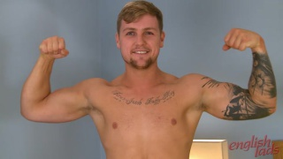 sexy blond gym trainer flexes his muscles