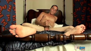 sexy young man rubs his feet and jacks off