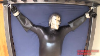 sub wearing rubber suit restrained to bed