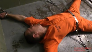 prisoner in orange coveralls chained to cell floor