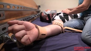 blindfolded man strapped to bed in his clothes