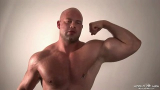 big beefy bald naked hunk flexing