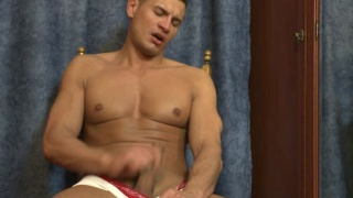 Muscular stud plays with his cock