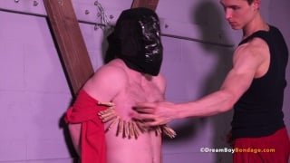 masked sub tied to wooden cross