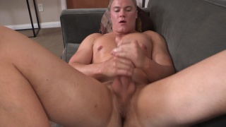 blond hunk jerking his dick on the sofa