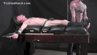 Muscular businessman strapped down on tickle table