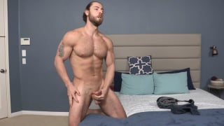 bearded guy kneels on bed and jerks his dick