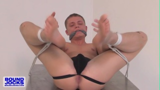 Bound Jock Micah Andrews tied to steel table