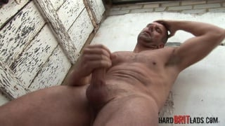 tall brit with shaved head jerks his uncut cock