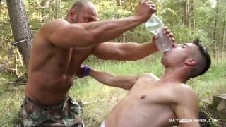 uniformed soldier uses naked prisoner outside