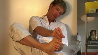 blond guy plays with his small feet