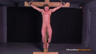 russian guy strung up on a wooden cross
