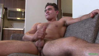 muscled stud jerks off on the couch