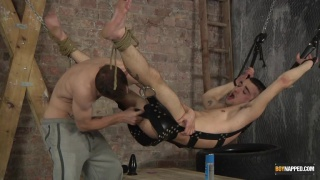 slave boy stripped naked and tied to a sling