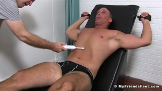 hunk strapped into the tickling chair