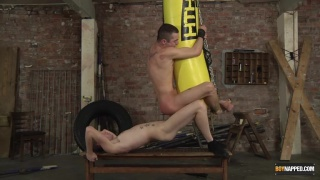 bottom gets fucked swinging from a punching bag