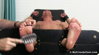 Austin Andrews gets bare feet tickled with hair brush