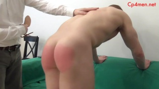 blond muscle boy's ass is bright red from spanking